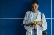 A college student looks down at her notebook and smiles because she'll leave college debt-free.
