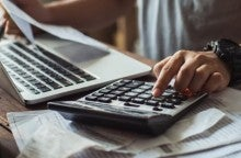 A woman calculates her medical bills at his desk and ponders medical bill myths.